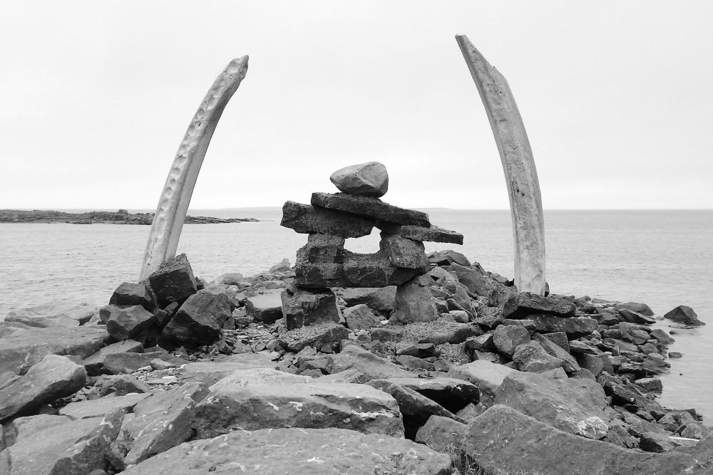 Inukshuk sculpture with whale jaw bones in Flowers Cove, NL by Picture Perfect Toursi